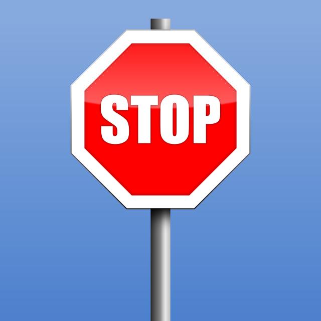 Segnale stradale di STOP su sfondo azzurro.